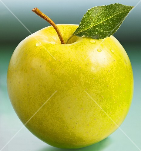 Golden Delicious apple with stalk and leaf