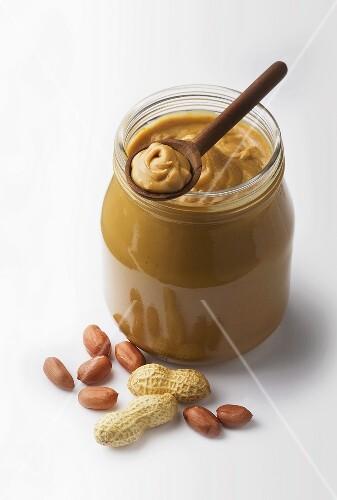 A jar of peanut butter with fresh peanuts