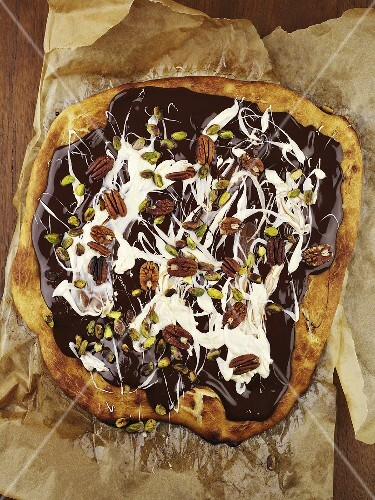 Pizza topped with chocolate sauce, cream and nuts