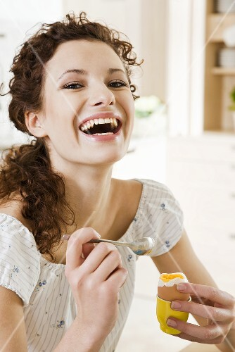 Young woman eating boiled egg for breakfast