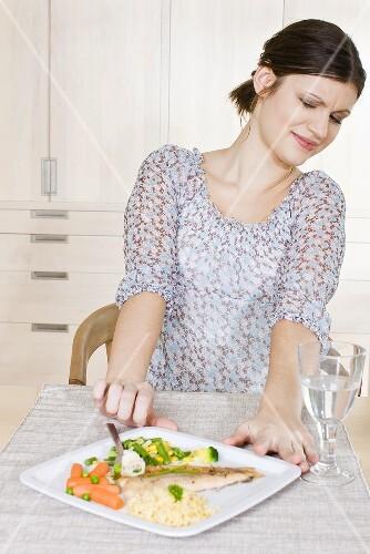 Frau schiebt Teller mit Fisch, Couscous und Gemüse von sich