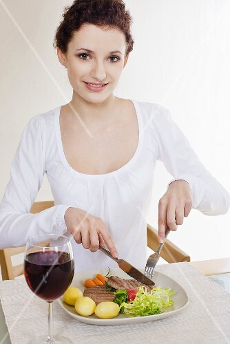 Young woman eating pork steak with boiled potatoes