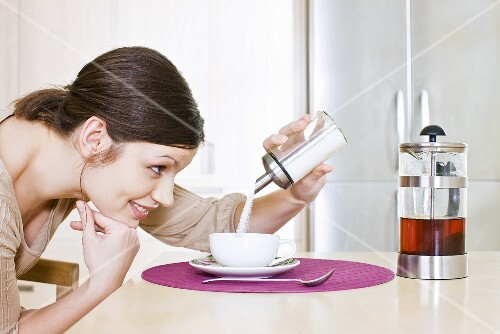 Young woman sweetening her tea with sugar