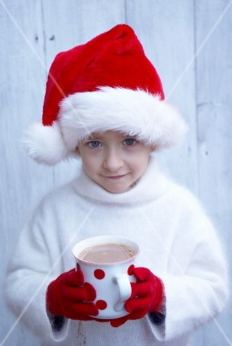 Small boy in Father Christmas hat holding mug of hot chocolate
