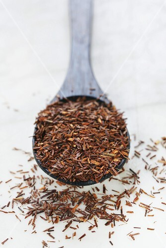 Rooibos tea leaves on wooden spoon