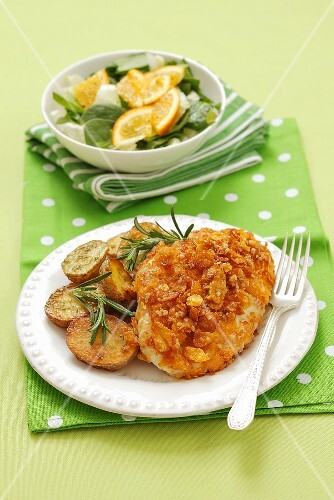 Chicken fillet covered with cornflakes with fried potatoes