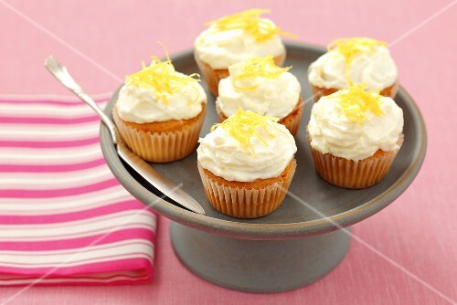 Mini muffins topped with cream cheese and lemon zest