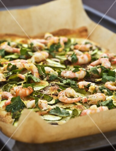 Pizza topped with prawns, vegetables & herbs on baking tray