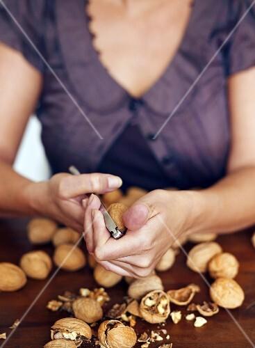 Woman cracking walnuts with nutcracker