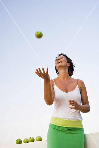Woman playing with a green apple out of doors