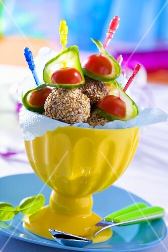 Sesame-coated meatballs, cucumber & tomatoes on cocktail sticks