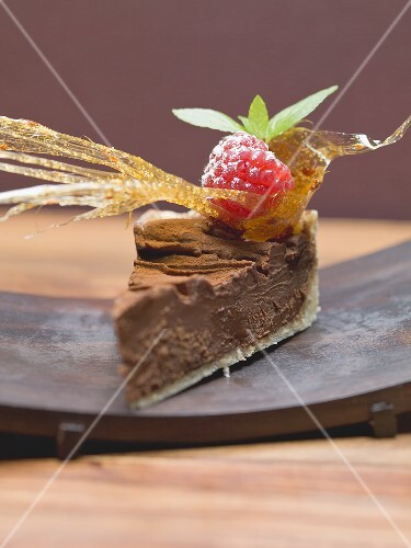 Piece of chocolate torte with a caramel fan and a raspberry