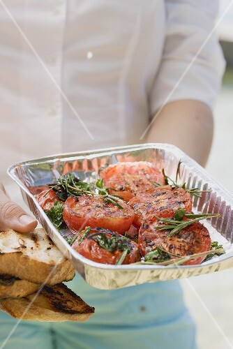 Woman holding an aluminium dish of grilled tomatoes