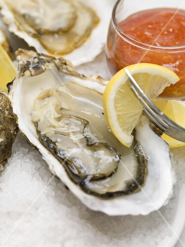 Fresh oysters with lemon and tomato sauce (close-up)