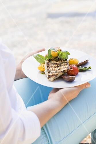 Frau hält Grillteller (Fischfilet mit Gemüse) im Freien
