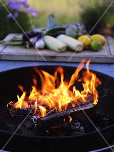 Burning charcoal, vegetables in background