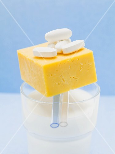 Tablets and Cheddar cheese on glass of milk