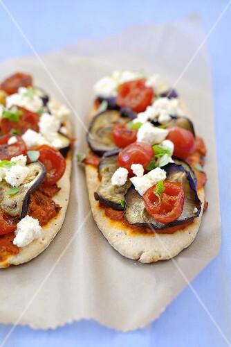 Two pita bread pizzas with aubergines, cherry tomatoes, feta