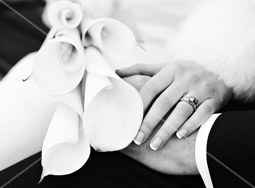 Bridal couple's hands with wedding bouquet