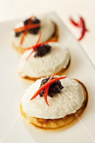 Blinis topped with goat's cheese and lumpfish roe
