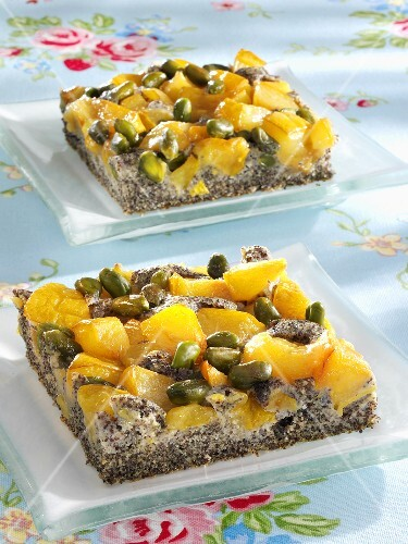Two pieces of mirabelle and poppy seed cake with pistachios