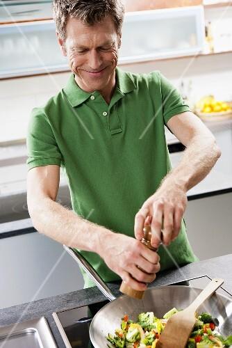 Man seasoning vegetables in wok