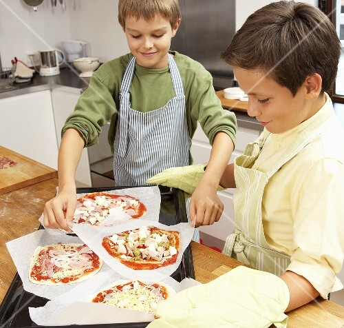 Two boys making pizzas