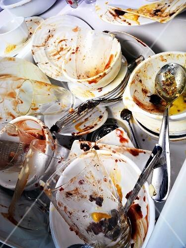 Schmutzige Teller, Gläser und Besteck im Spülbecken