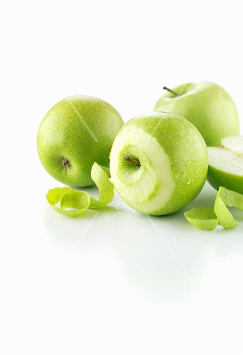 Green apples, one partly peeled