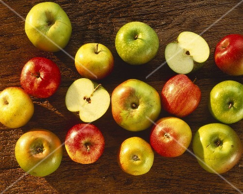 Various types of apples on a wooden surface