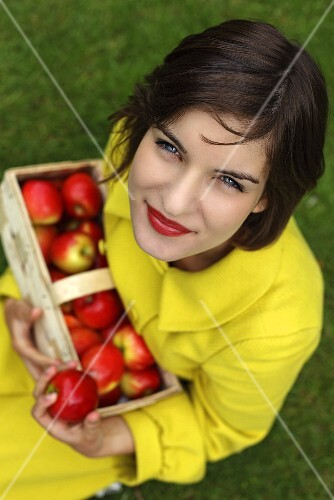 Woman holding a basket of fresh red apples