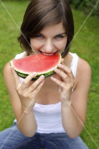 Young woman biting into a slice of watermelon