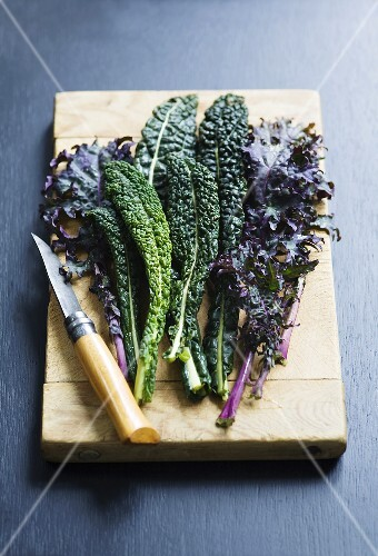 Leaves of various types of kale on wooden board with knife