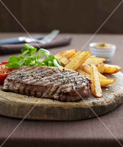 Beefsteak with chips on rustic wooden board