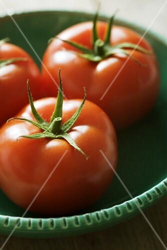 Three tomatoes in ceramic bowl
