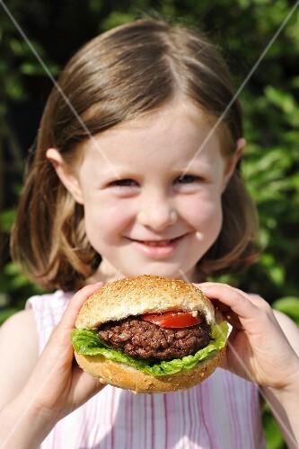 A girl holding a hamburger