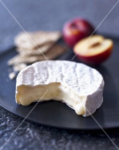 Camembert, crisp breads and plums