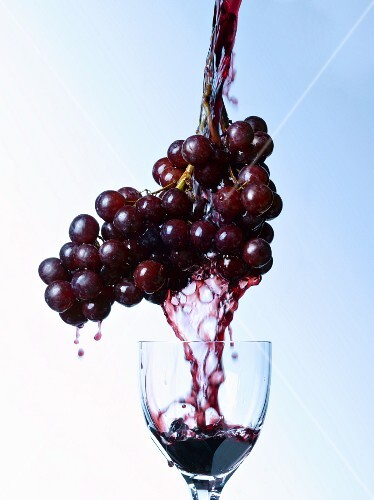 Red wine being poured into a wine glass over red grapes
