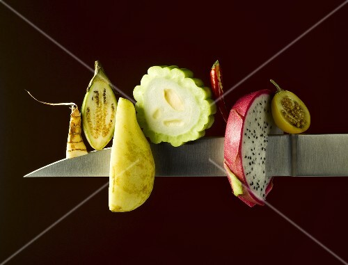 Various exotic fruits and vegetables on a knife