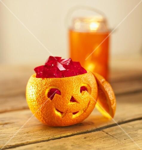 Fruchtgeleewürfel in ausgehöhlter Orange für Halloween