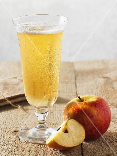 A glass of cider with apple