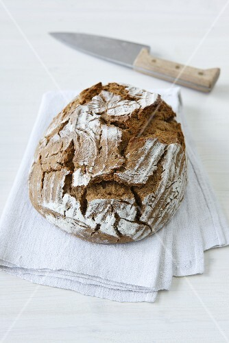 Crusty bread on a linen cloth with a knife