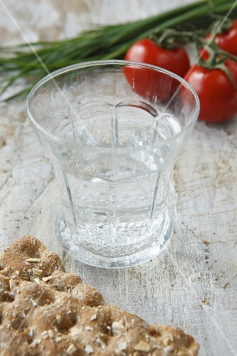 A glass of water, crispbread, tomatoes and chives