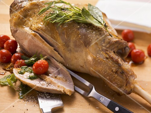 Roast leg of lamb with herb pesto and cherry tomatoes