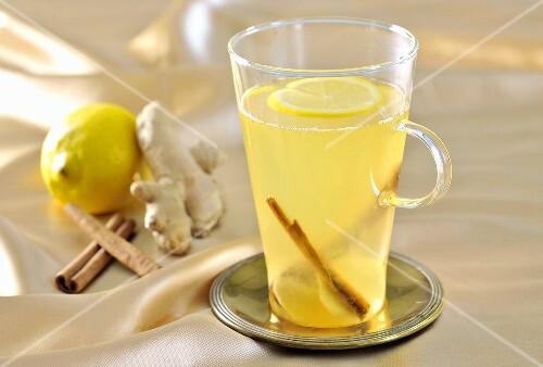 A glass of ginger tea with lemons and cinnamon
