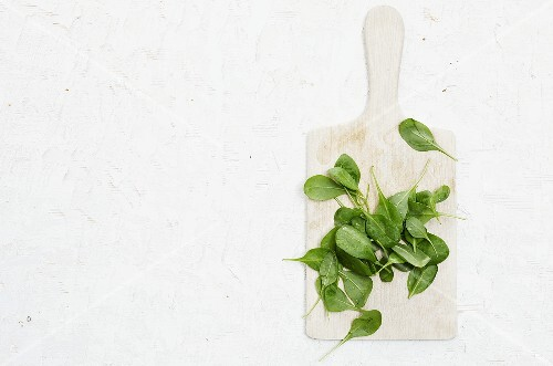 Spinach leaves on a chopping board