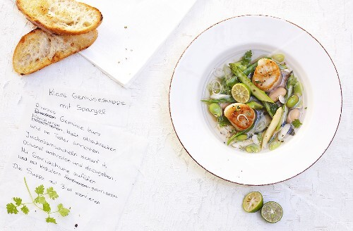Clear vegetable soup with asparagus and scallops