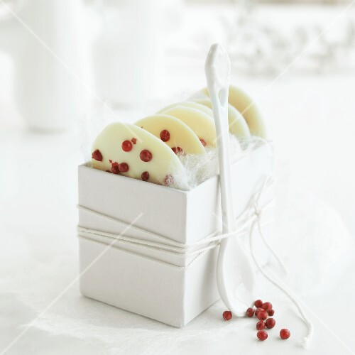White chocolate 'taler' (coins) with red pepper corns