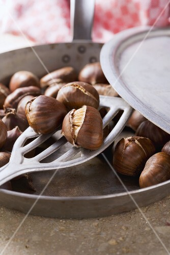 Roast chestnuts being taken out of a pan