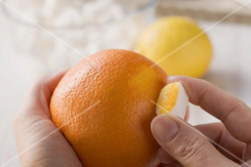 Sugar cubes being flavoured: rubbing onto an orange